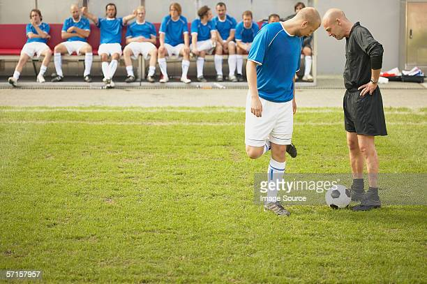 referee talking to footballer - fußballtrikot stock-fotos und bilder