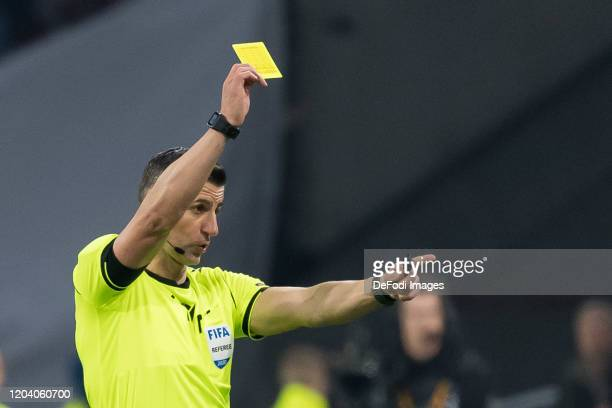 Referee Tasos Sidiropoulos shows the yellow card during the UEFA Europa League round of 32 second leg match between AFC Ajax and Getafe CF at...