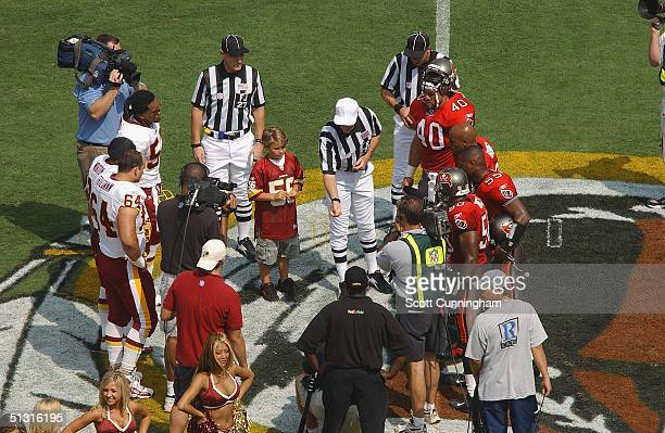 Referee Terry McAulay conducts the coin toss in front of team captains before the game between the Tampa Bay Buccaneers and the Washington Redskins...