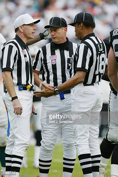 Referee Terry McAulay umpire Ed Coukart and line judge Byron Boston huddle to discuss the play during the NFL game between the Oakland Raiders and...