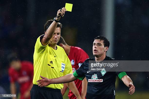 Referee Thorsten Kinhoefer shows a yellow card to Zlatko Junuzovic of Bremen during the Bundesliga match between SC Freiburg and SV Werder Bremen at...
