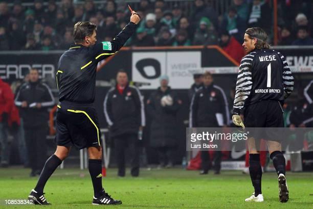 Referee Thorsten Kinhoefer shows goalkeeper Tim Wiese of Bremen the red card during the Bundesliga match between SV Werder Bremen and FC Bayern...