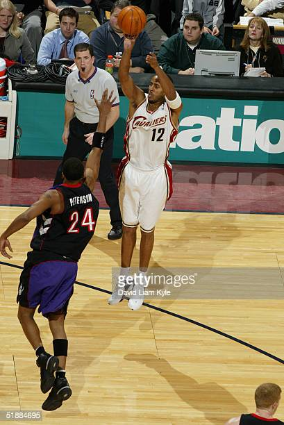 Referee Tim Donaghy watches as Lucious Harris of the Cleveland Cavaliers shoots over Morris Peterson of the Toronto Raptors during the game on...