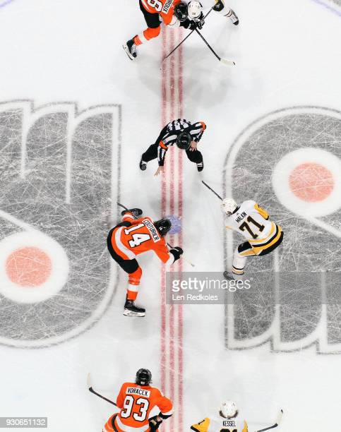 Referee Tim Peel drops the puck on a faceoff between Evgeni Malkin of the Pittsburgh Penguins and Sean Couturier of the Philadelphia Flyers on March...