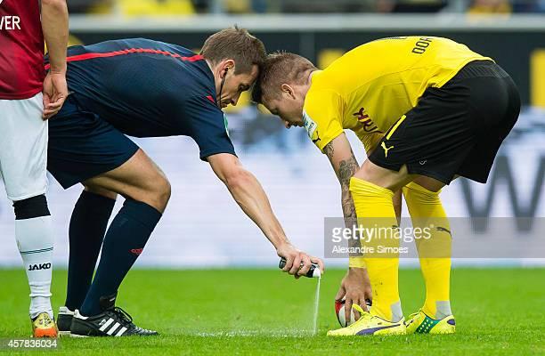 Referee Tobias Spieler uses the vanishing spray while Marco Reus of Borussia Dortmund waits during the Bundesliga match between Borussia Dortmund and...
