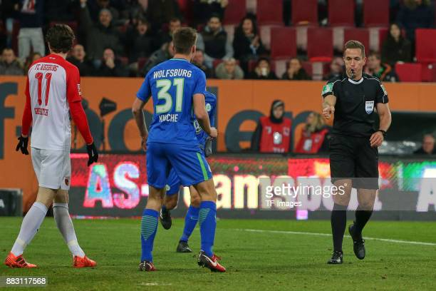 Referee Tobias Stieler gestures and Michael Grogoritsch of Augsburg and Robin Knoche of Wolfsburg look on during the Bundesliga match between FC...