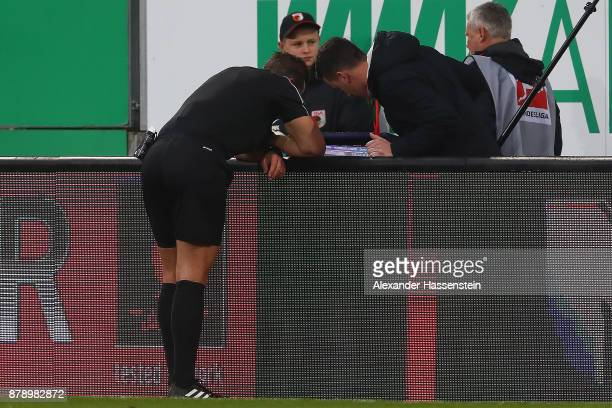 Referee Tobias Stieler is checking a foul on the monitors during the Bundesliga match between FC Augsburg and VfL Wolfsburg at WWKArena on November...