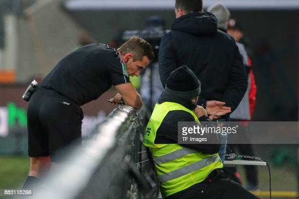 Referee Tobias Stieler looks on the screen during the Bundesliga match between FC Augsburg and VfL Wolfsburg at WWKArena on November 25 2017 in...