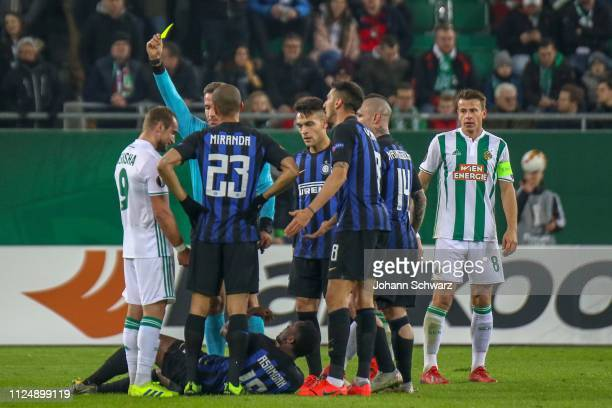 Referee Tobias Stieler of Germany shows a yellow card to Veton Berisha of Rapid during the UEFA Europa League Round of 32 match between SK Rapid Wien...