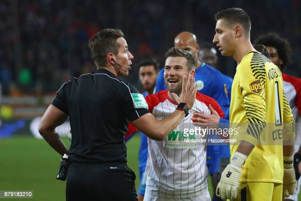 Referee Tobias Stieler reacts with Daniel Baier of Augsburg and Koen Casteels keeper of Wolfsburg during the Bundesliga match between FC Augsburg and...