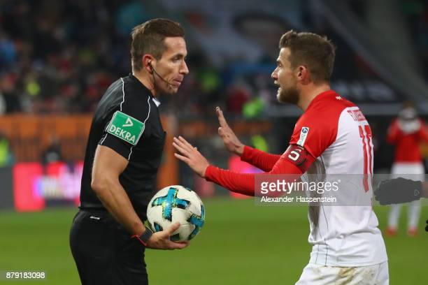 Referee Tobias Stieler reacts with Daniel Baier of Augsburg during the Bundesliga match between FC Augsburg and VfL Wolfsburg at WWKArena on November...