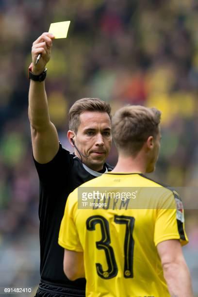 Referee Tobias Stieler show Erik Durm of Dortmund a yellow card during the Bundesliga match between Borussia Dortmund and FC Koeln at Signal Iduna...