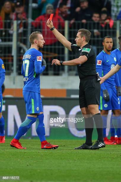 Referee Tobias Stieler shows a red card to Maximilian Arnold of Wolfsburg during the Bundesliga match between FC Augsburg and VfL Wolfsburg at...
