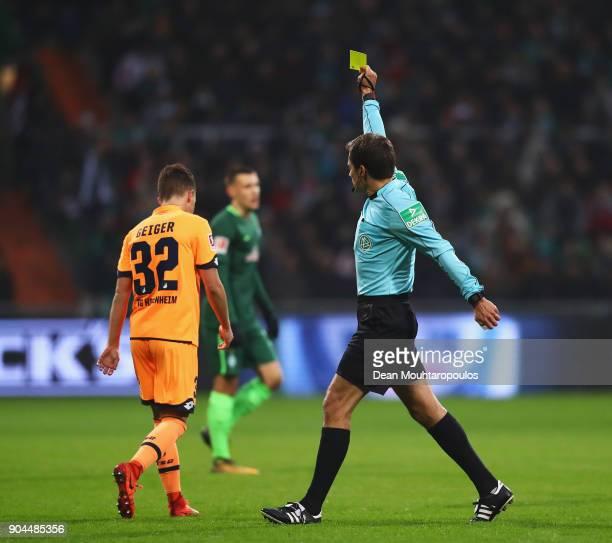 Referee Tobias Stieler shows a yellow card to Dennis Geiger of TSG 1899 Hoffenheim during the Bundesliga match between SV Werder Bremen and TSG 1899...