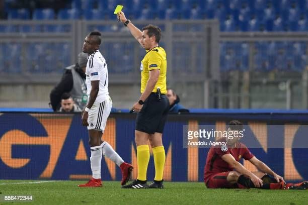 Referee Tobias Stieler shows a yellow card to Donald Guerrier of Qarabag FK during the UEFA Champions League Group C soccer match between AS Roma and...