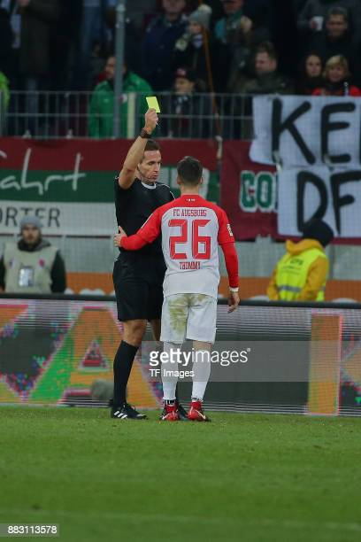 Referee Tobias Stieler shows a yellow card to Eric Thommy of Augsburg during the Bundesliga match between FC Augsburg and VfL Wolfsburg at WWKArena...