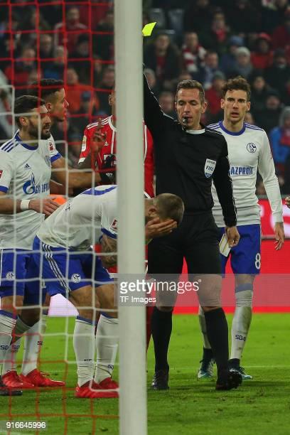 Referee Tobias Stieler shows a yellow card to Guido Burgstaller of Schalke during the Bundesliga match between FC Bayern Muenchen and FC Schalke 04...