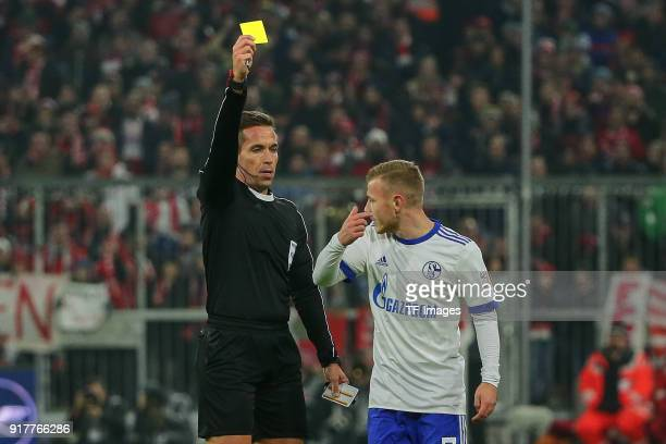 Referee Tobias Stieler shows a yellow card to Max Meyer of Schalke during the Bundesliga match between FC Bayern Muenchen and FC Schalke 04 at...