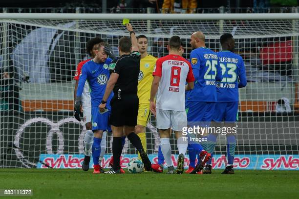 Referee Tobias Stieler shows a yellow card to Maximilian Arnold of Wolfsburg during the Bundesliga match between FC Augsburg and VfL Wolfsburg at...