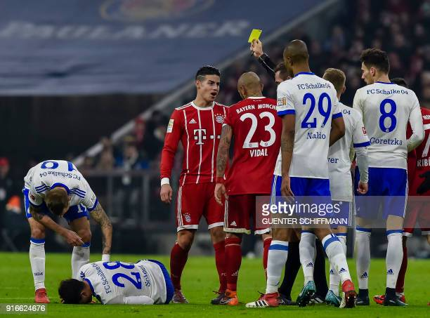 Referee Tobias Stieler shows Bayern Munich's Columbian midfielder James Rodriguez the yellow card during the German first division Bundesliga...