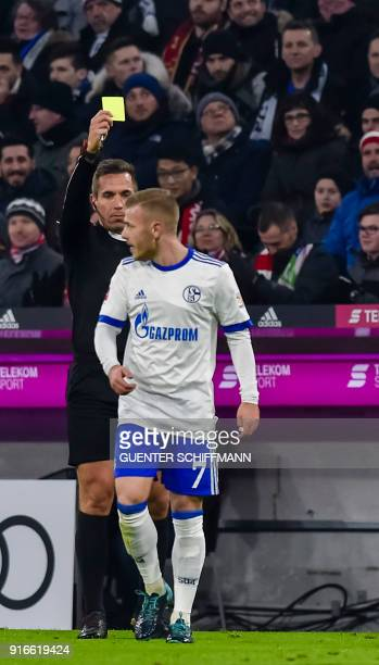 Referee Tobias Stieler shows Schalke's German midfielder Max Meyer the yellow card during the German first division Bundesliga football match FC...