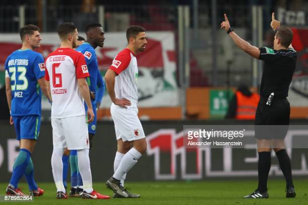 Referee Tobias Stieler signals that he is going to check a foul on the monitors during the Bundesliga match between FC Augsburg and VfL Wolfsburg at...
