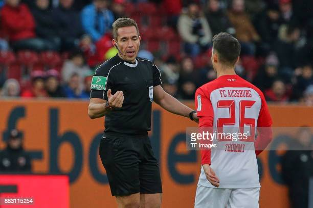 Referee Tobias Stieler speaks with Eric Thommy of Augsburg during the Bundesliga match between FC Augsburg and VfL Wolfsburg at WWKArena on November...