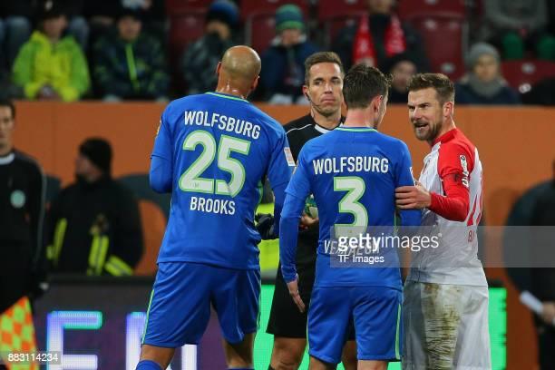 Referee Tobias Stieler speaks with John Anthony Brooks of Wolfsburg Paul Verhaegh of Wolfsburg and Daniel Baier of Augsburg during the Bundesliga...