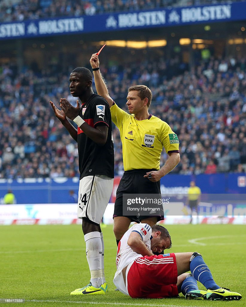 Referee Tobias Welz (R) shows the red card to Antonio Ruediger (L) of Stuttgart next to Rafael van der Vaart of Hamburg during the Bundesliga match between Hamburger SV and VfB Stuttgart at Imtech Arena on October 20, 2013 in Hamburg, Germany.