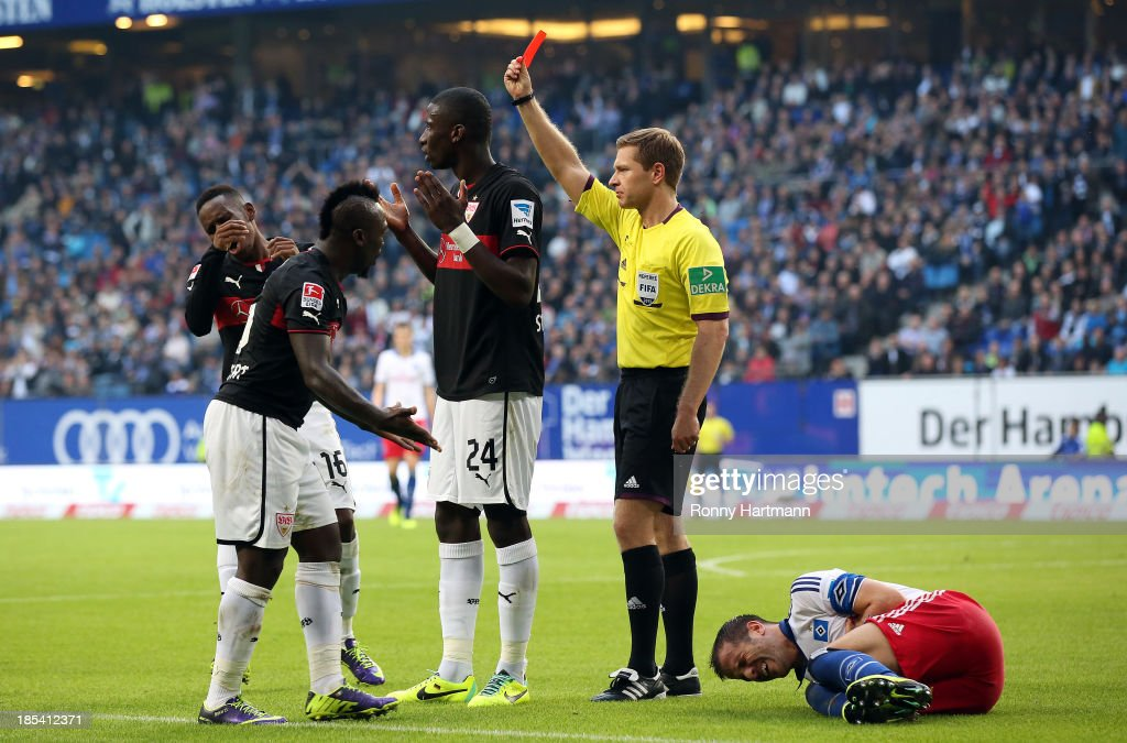 Referee Tobias Welz (2nd R) shows the red card to Antonio Ruediger (C) of Stuttgart next to Rafael van der Vaart (R) of Hamburg during the Bundesliga match between Hamburger SV and VfB Stuttgart at Imtech Arena on October 20, 2013 in Hamburg, Germany.