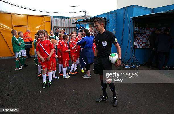 Referee Tom Harald Hagen of Norway waits with the mascots to lead out the players from Northern Ireland and Russia prior to the FIFA 2014 World Cup...