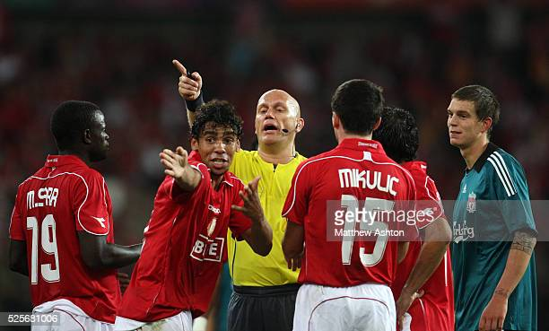 Referee Tom Henning Ovrebo from Norway waves away protests from Standard Liege players after he awarded Liverpool a free kick in the second half