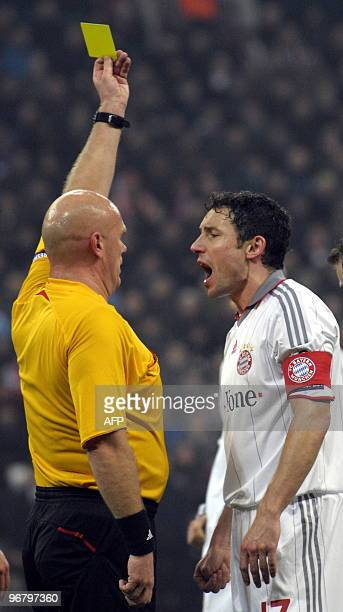 Referee Tom Henning Ovrebo gives Bayern Munich's Dutch midfielder Mark van Bommel a yellow card during the 1st leg UEFA Champions League football...