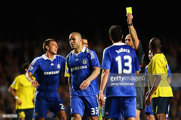 Referee Tom Henning Ovrebo shows Alex of Chelsea a yellow card during the UEFA Champions League Semi Final Second Leg match between Chelsea and...