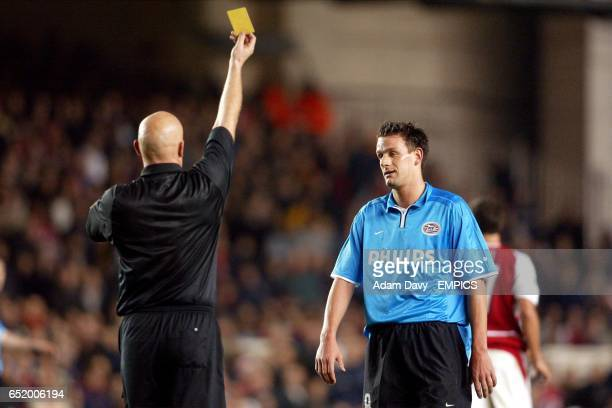 Referee Tom Henning Ovrebo shows the yellow card to PSV Eindhoven's Jan Vennegoor of Hesselink