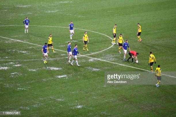 Referee Tom Nield picks up the ball to postpone the game due to poor weather conditions during the Sky Bet Leauge One match between Oxford United and...