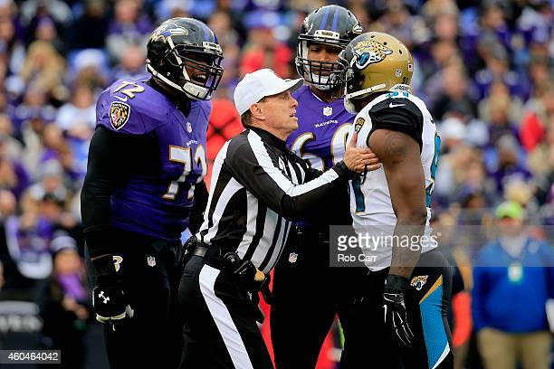 Referee Tony Corrente breaks up an altercation between guard Kelechi Osemele of the Baltimore Ravens and defensive end Chris Clemons of the...