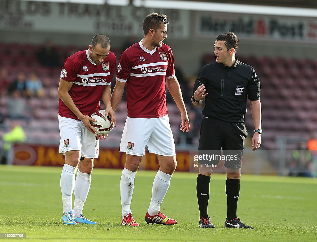 Referee Tony Harrington talks to Darren Carter of Northampton Town as team mate Chris Hackett prepares to take a free kick during the Sky Bet League Two match between Northampton Town and Dagenham & Redbridge at Sixfields Stadium on October 19, 2013 in Northampton, England.