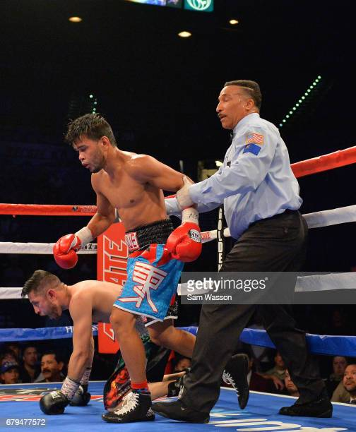 Referee Tony Weeks sends Jesus Rojas to a neutral corner after he knocked down Abraham Lopez during their featherweight fight at MGM Grand Garden...