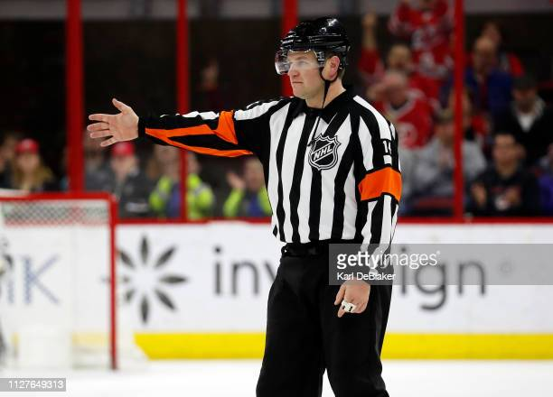 Referee Trevor Hanson returns to center ice after reviewing a play to indicate a goal for the Carolina Hurricanes in an NHL game against the Los...