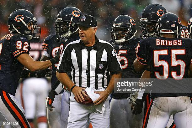 A referee tries to keep the football dry as the Chicago Bear defense including Hunter Hillenmeyer Anthony Adams and Lance Briggs await the start of...