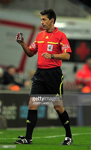 Referee Turienzo Alvarez holds a can thrown by a supporter during the Spanish league football match RCD Espanyol vs FC Barcelona on January 8 2012 at...
