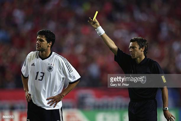 Referee Urs Meier of Switzerland shows the yellow card to Michael Ballack of Germany which due to a previous booking means he will miss the final...