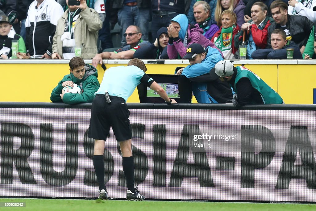Referee uses a video assistant to decide about penalty during the Bundesliga match between Borussia Moenchengladbach and Hannover 96 at Borussia-Park on September 30, 2017 in Moenchengladbach, Germany.