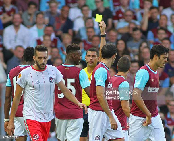 Referee Vadims Direktorenko shows a yellow card to Reece Oxford of West Ham during the UEFA Europa League match between West Ham United and FC...