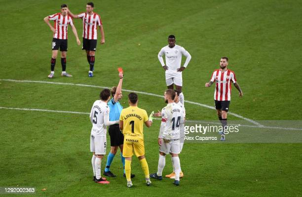 Referee Valentin Gomez gives Jorge Pulido of Huesca a red card during the La Liga Santander match between Athletic Club and SD Huesca at Estadio de...
