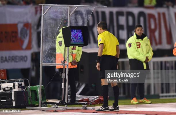 Referee Victor Carrillo of Peru reviews a play on the VAR during a match between River Plate and Cerro Porteño as part of Quarter Finals of Copa...