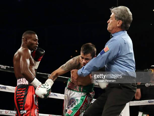 Referee Vik Drakulich grabs Moises Flores as Guillermo Rigondeaux looks on after their super bantamweight championship bout at the Mandalay Bay...