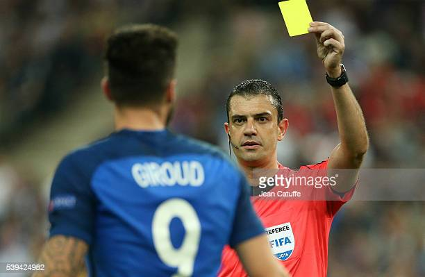 Referee Viktor Kassai of Hungary delivers a yellow card to Olivier Giroud of France during the UEFA Euro 2016 Group A opening match between France...