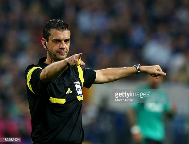Referee Viktor Kassai signals during the UEFA Champions League Group E match between FC Schalke 04 and Chelsea at VeltinsArena on October 22 2013 in...